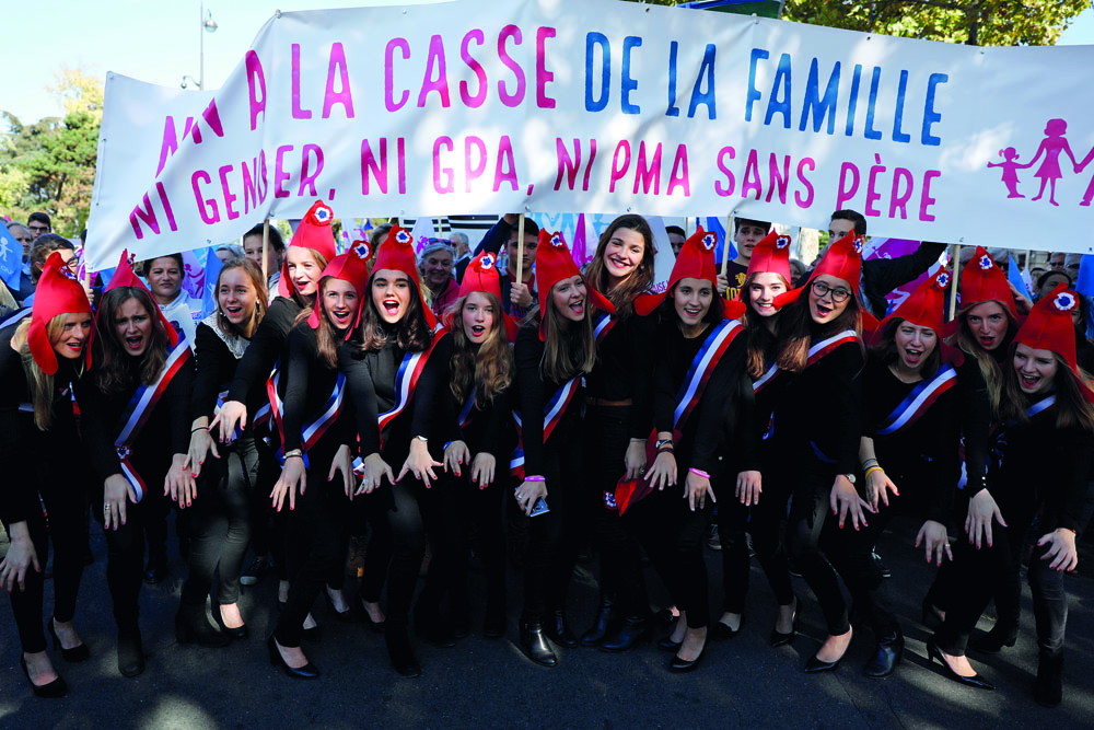 "Women wearing Revolution Phrygian caps take part in the ""La Manif Pour Tous"" (Demonstration For All) to protest against PMA (Procreation Medicalement Assistee or Medically Assisted Reproduction) and GPA (Grossesse pour Autrui or Gestation for Others) during a march in Paris, France, October 16, 2016. REUTERS/Benoit Tessier - RTX2P1WV"